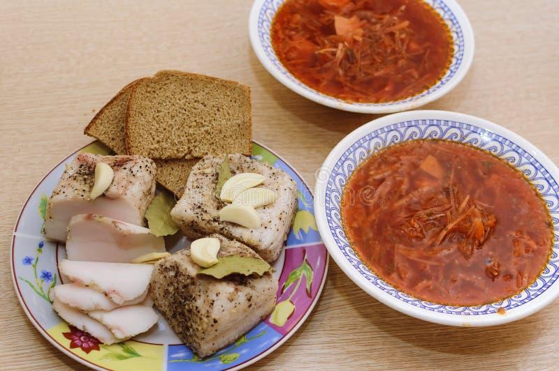 与胡椒和月桂叶和黑面包谎言的被盐溶的猪油在一块板材,在它旁边那里是两块板材用红色罗宋汤 特写镜头, 图库摄影