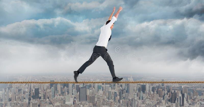 与胳膊的商人提高了走在绳索反对都市风景 免版税图库摄影
