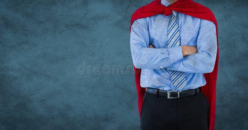 与胳膊的商人超级英雄中间部分折叠了反对蓝色背景和难看的东西覆盖物 免版税图库摄影
