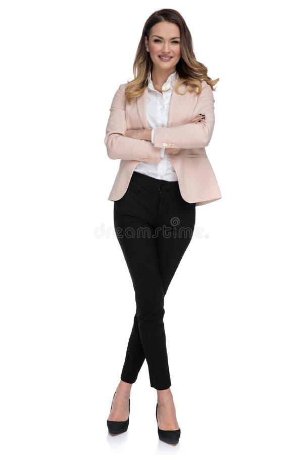 与胳膊的确信的女实业家立场折叠了和盘的腿 免版税库存图片