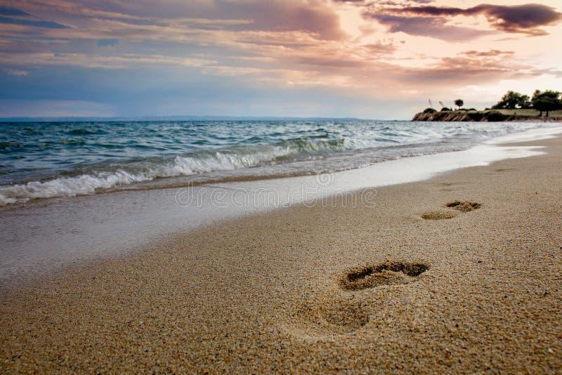 与脚印的沙滩在沙子、蓝色波浪海和多云天空在黄昏 库存图片