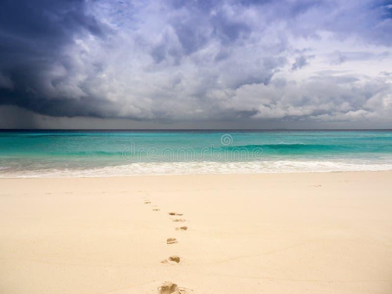 与脚印的风雨如磐的海滩在沙子 库存图片