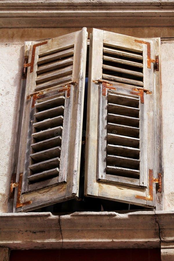 与腐烂的老窗口和盖历史大厦木快门在普拉,克罗地亚,特写镜头/大厦门面的元素 免版税库存图片