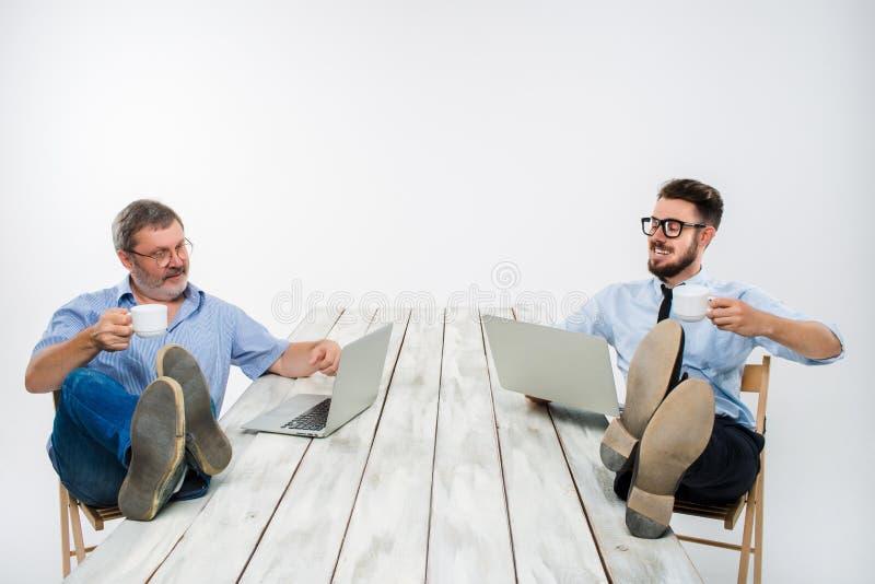 与腿的两个商人在研究膝上型计算机的桌 库存图片