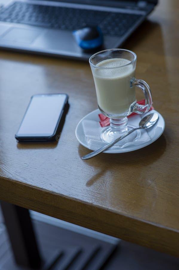 与膝上型计算机、一杯咖啡和一只老鼠的工作区膝上型计算机的,电话,在一张白色木桌上的玻璃 免版税库存图片