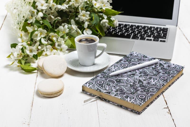 与膝上型计算机、一杯茶和花的工作区在木背景 家庭办公室构成,自由职业者的概念 免版税库存照片