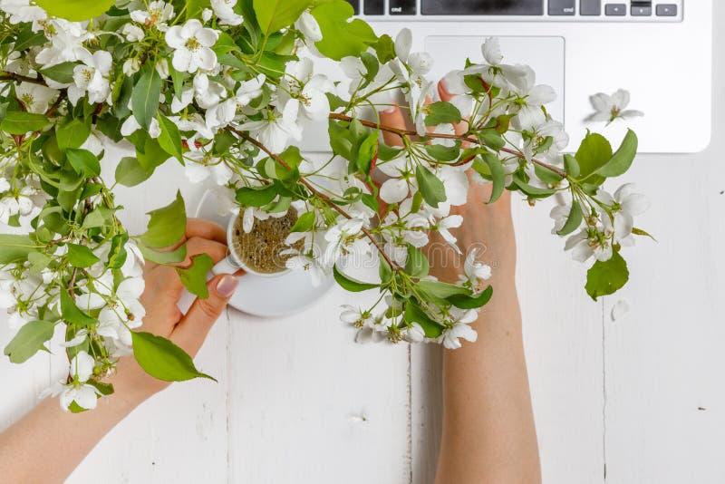 与膝上型计算机、一杯茶和花的工作区在木背景 家庭办公室构成,自由职业者的概念 库存照片