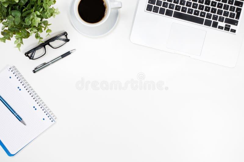 与膝上型计算机、咖啡杯和供应顶视图的办公桌桌 库存图片