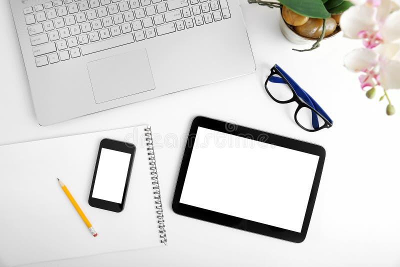 与膝上型计算机、空白的数字式片剂和智能手机的工作区 库存图片