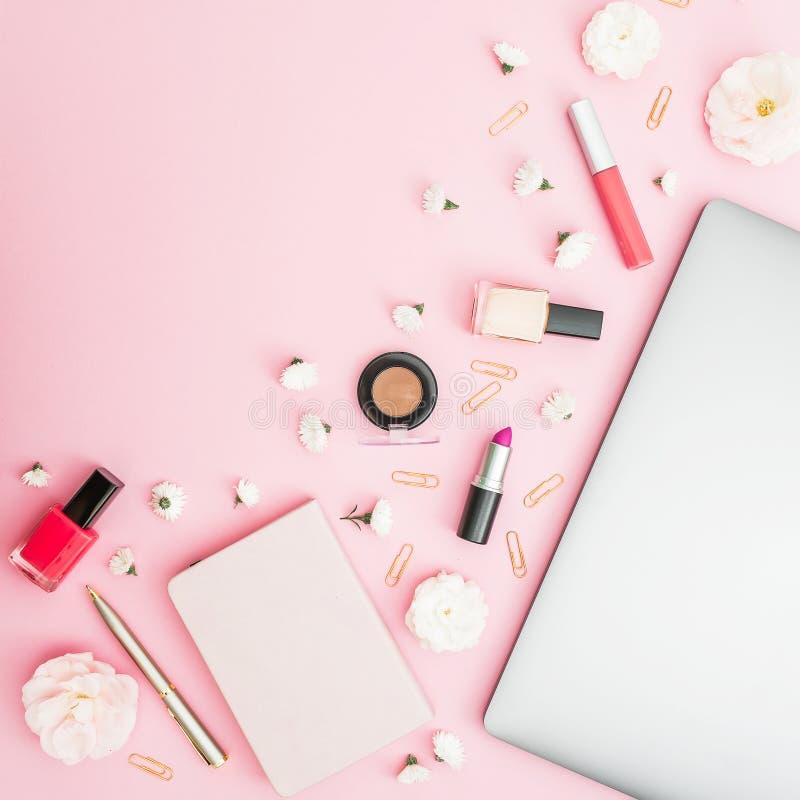 与膝上型计算机、笔记本、化妆用品和花的办公室女性书桌工作区在桃红色背景 顶视图 平的位置生活方式conce 库存照片