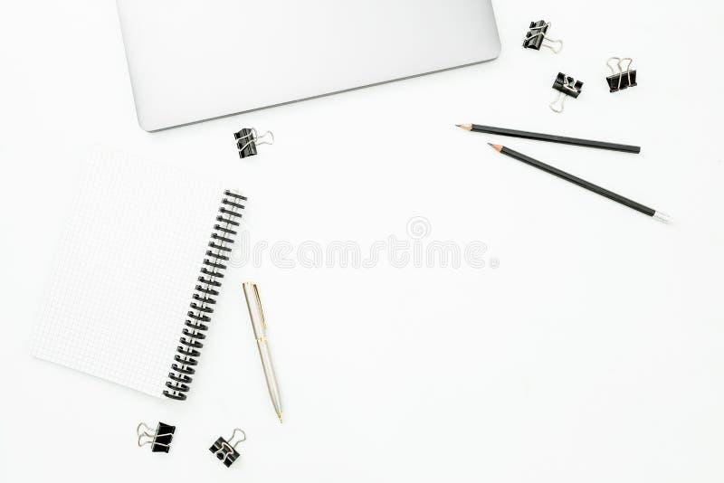 与膝上型计算机、笔记本和笔的家庭办公室桌面工作区在白色桌上 顶视图 平的位置生活方式概念 免版税库存图片