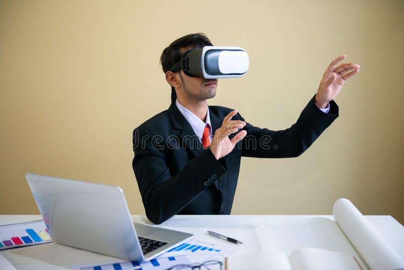 与膝上型计算机一起使用和使用虚拟现实玻璃的商人 免版税图库摄影