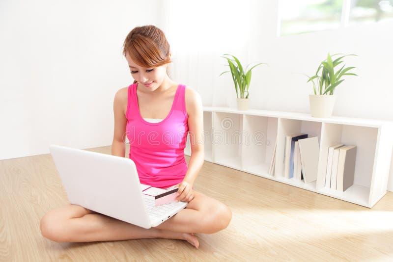 与膝上型计算机和信用卡的美好的妇女购物 免版税图库摄影
