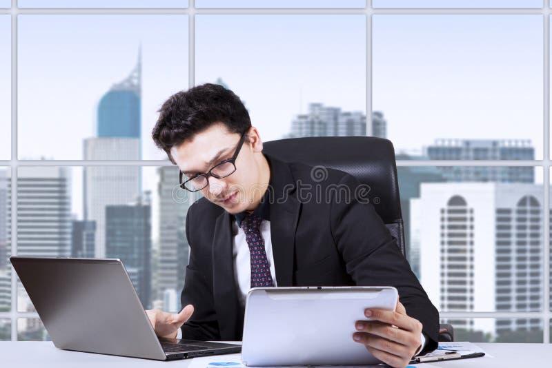 与膝上型计算机和数字式片剂的严肃的商人 库存照片