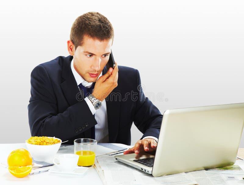 与膝上型计算机和早餐的生意人 免版税库存照片