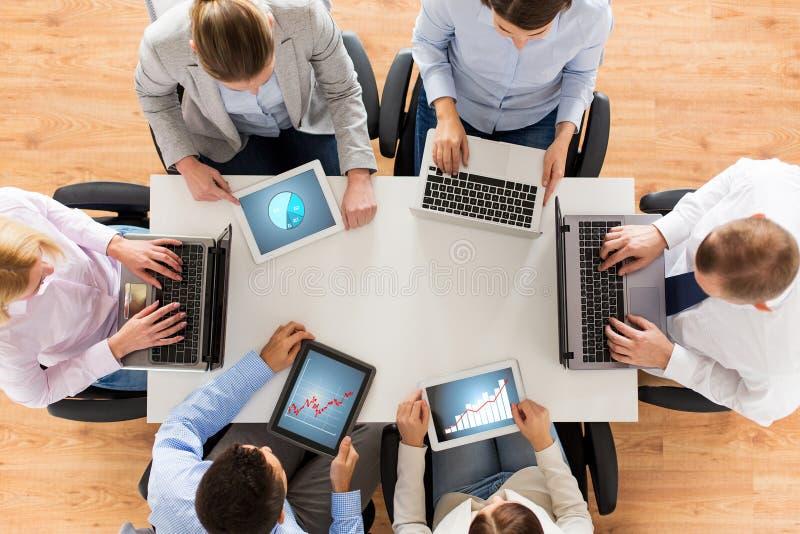 与膝上型计算机和片剂个人计算机的企业队 库存照片