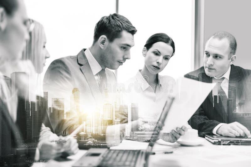 与膝上型计算机和纸的企业队在办公室 库存照片