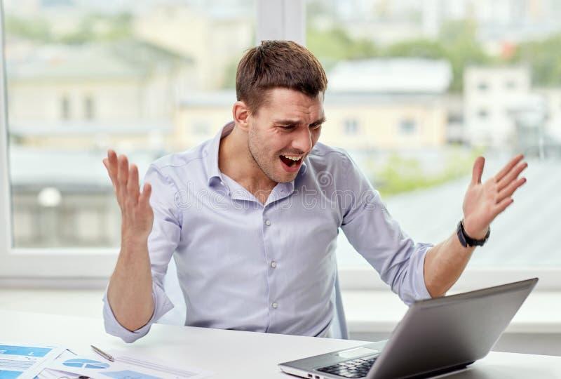 与膝上型计算机和纸的恼怒的商人在办公室 免版税库存照片
