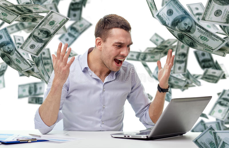 与膝上型计算机和落的金钱的恼怒的商人 库存图片