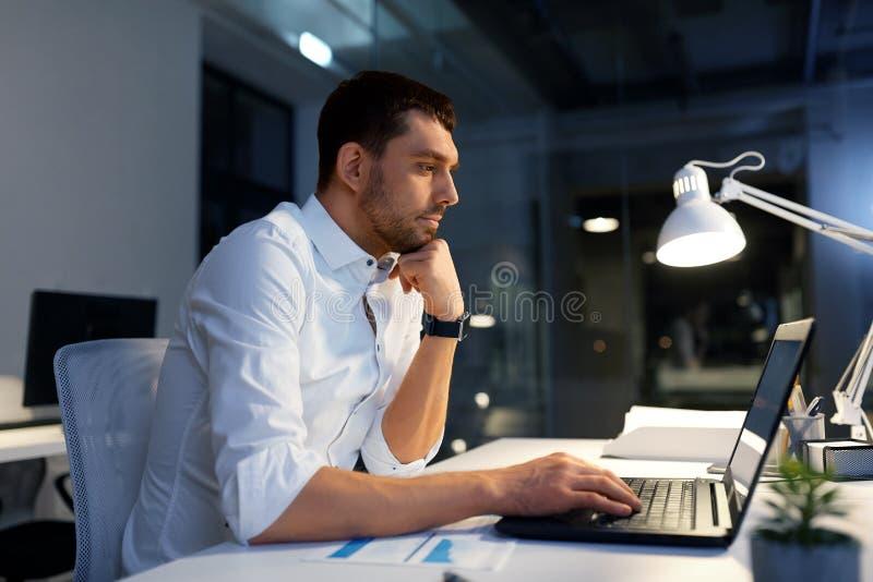 与膝上型计算机工作的商人在夜办公室 免版税库存图片