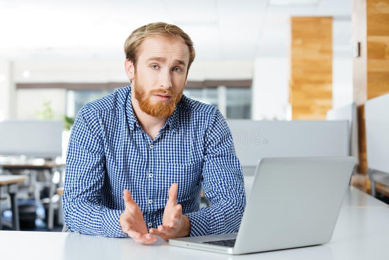 与膝上型计算机的严肃的商人坐和谈话在办公室 库存照片
