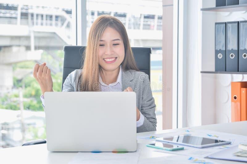 与膝上型计算机的亚洲企业工作和举胳膊的有成功以后得到喜讯 免版税库存图片