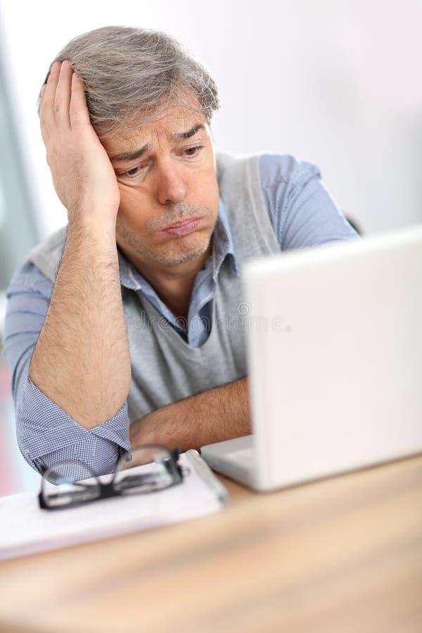 与膝上型计算机的关心的成熟商人 库存图片