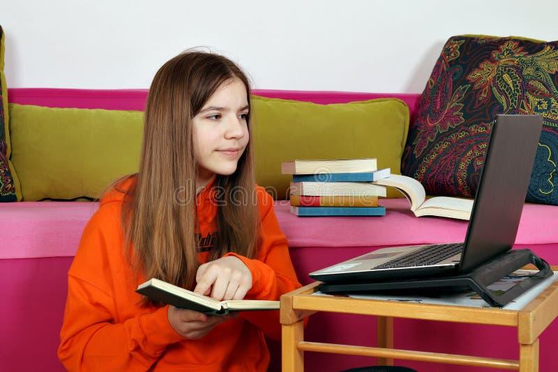 与膝上型计算机的十几岁的女孩研究 免版税库存照片