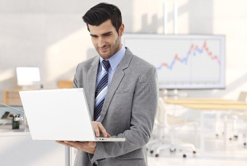 与膝上型计算机的商人在会议室 免版税库存图片