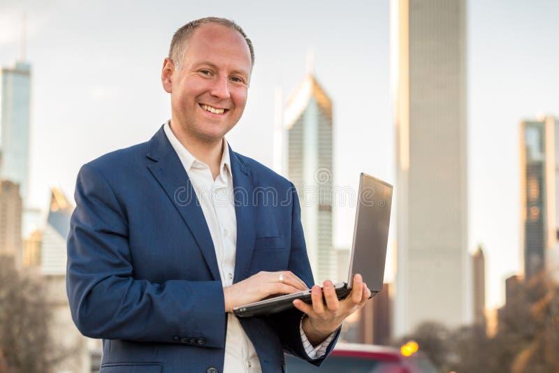 与膝上型计算机的商人在办公楼前面 免版税图库摄影
