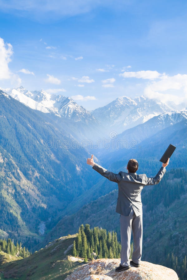 与膝上型计算机的商人在山顶部请是 免版税库存图片