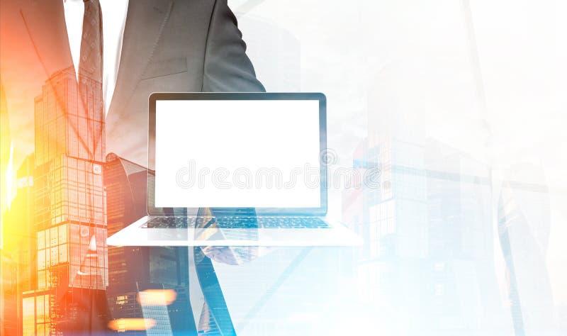 与膝上型计算机的商人在有雾的城市 免版税库存照片