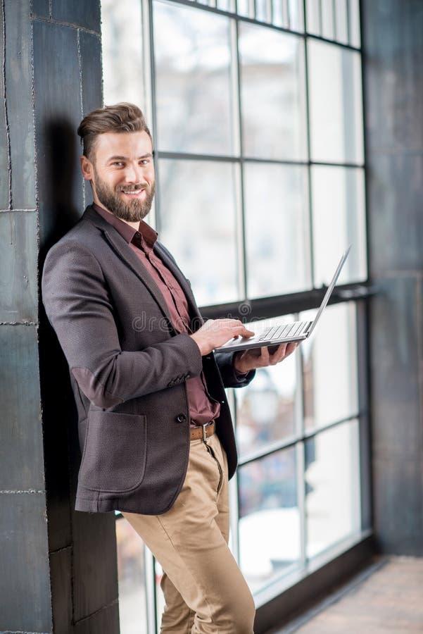 与膝上型计算机的商人在窗口附近 免版税库存图片