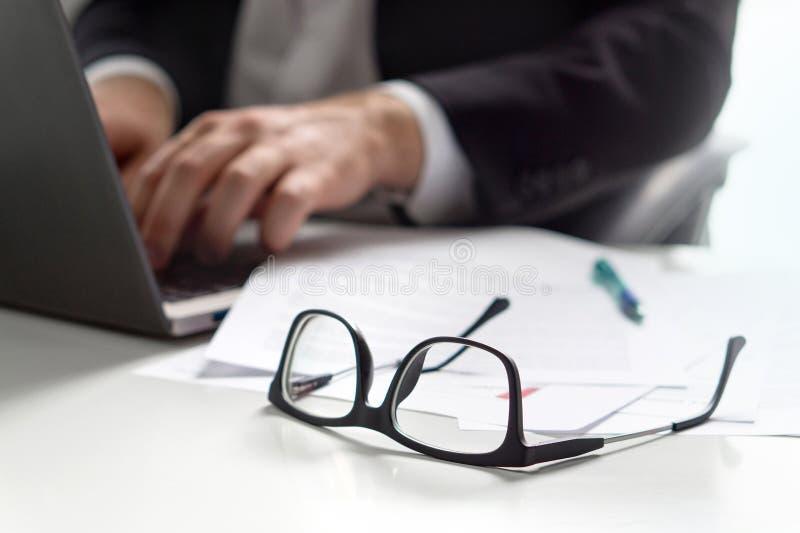 与膝上型计算机的商人文字在办公室 免版税库存照片