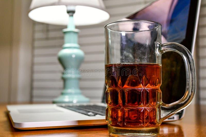 与膝上型计算机的在家工作站,杯子用一个饮料和一盏灯填装了心情照明设备的,当在网上时工作 免版税库存照片