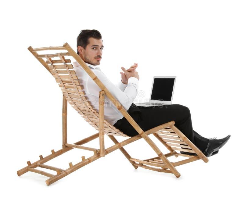与膝上型计算机的年轻商人在反对白色背景的太阳懒人 ?? 免版税库存照片