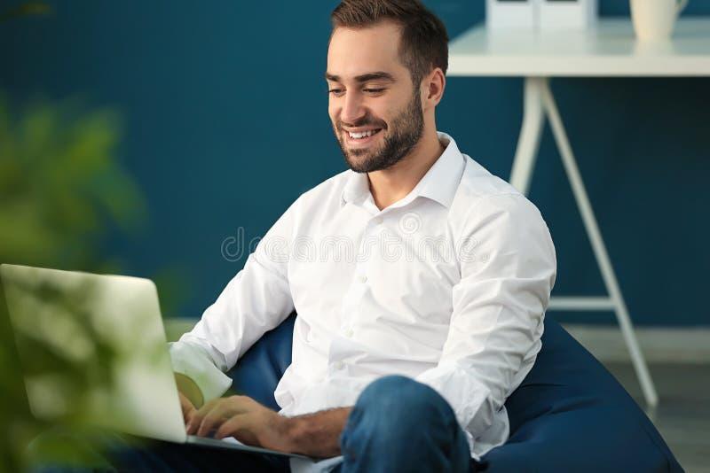 与膝上型计算机的年轻商人坐装豆子小布袋椅子在办公室 库存图片