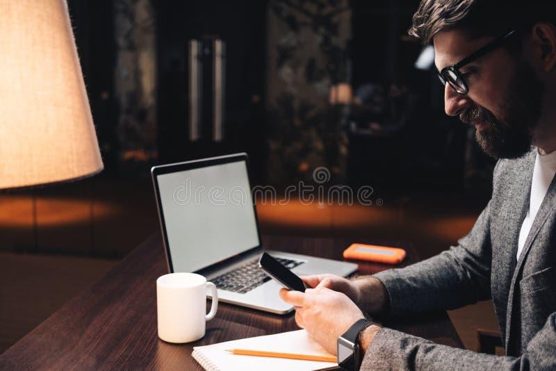 与膝上型计算机的微笑的使用智能手机的商人和smartwatch在晚上向高处发射coworking的演播室 有胡子的经理由木坐 免版税图库摄影