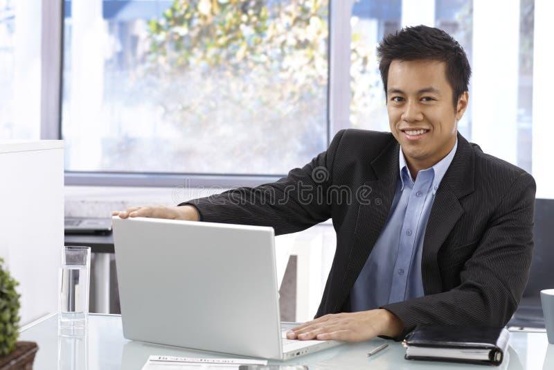 与膝上型计算机的愉快的生意人 库存图片