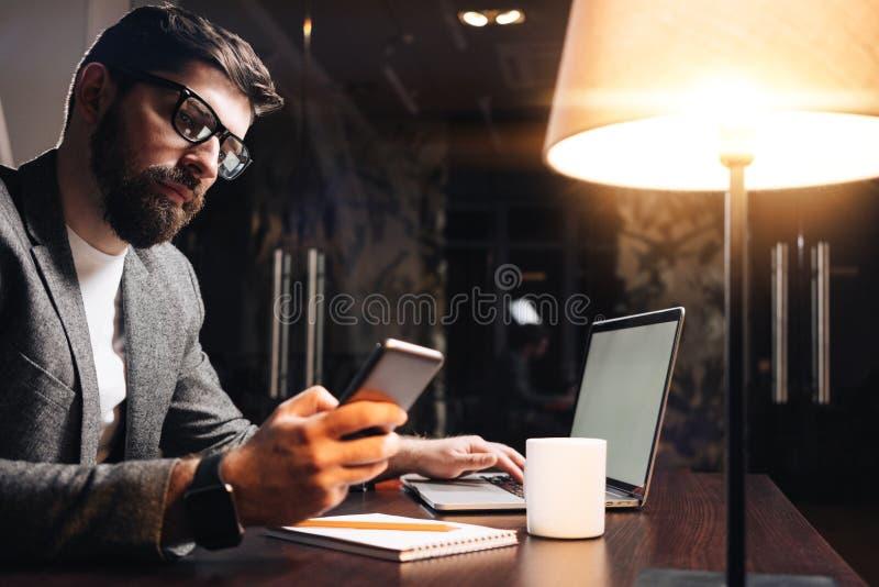与膝上型计算机的有胡子的商人使用手机在夜顶楼办公室 年轻在当代智能手机的人键入的文本 Worki 免版税库存图片
