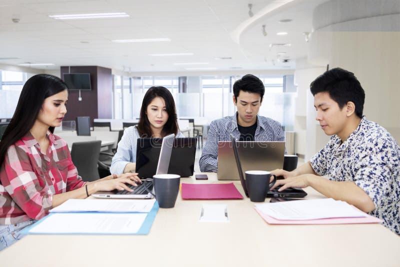 与膝上型计算机的繁忙的自由职业者团队工作在办公室 免版税库存照片