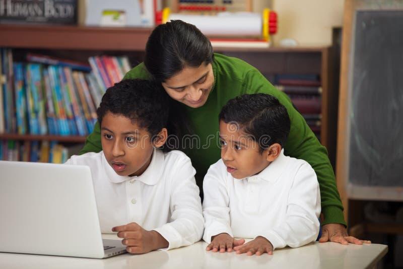 与膝上型计算机的西班牙家庭在家庭学校设置 库存图片