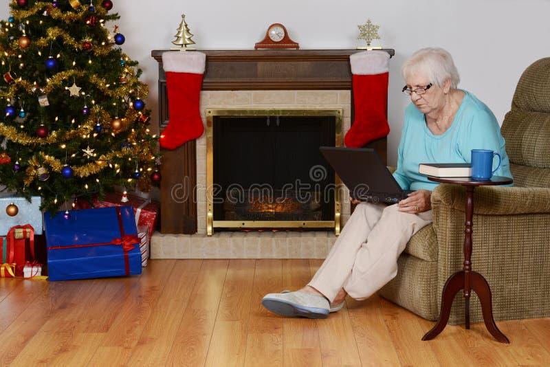 与膝上型计算机的资深妇女圣诞节购物 库存图片