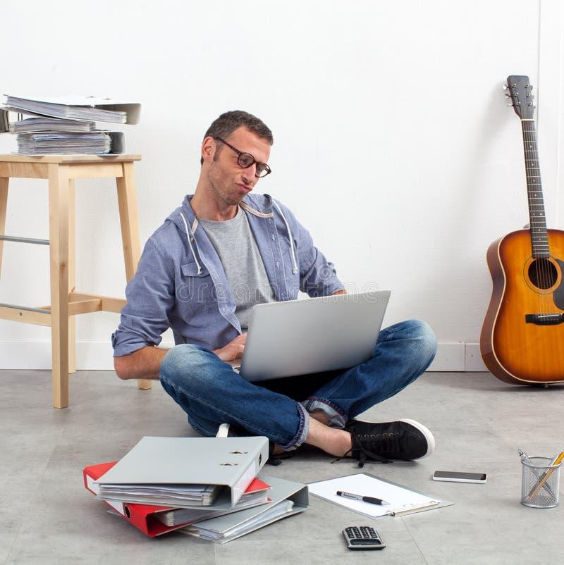 与膝上型计算机的起始的企业家运用预算在家庭办公室 库存照片