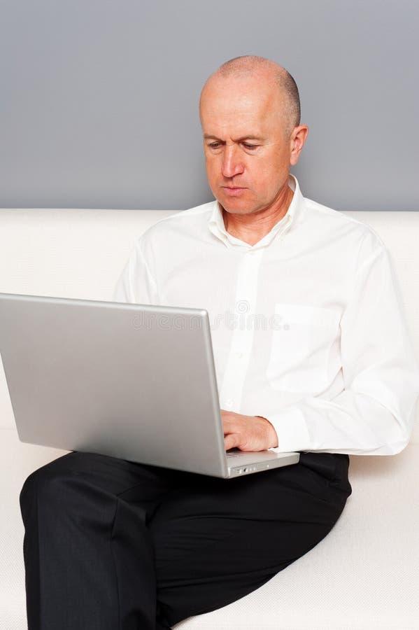 与膝上型计算机的高级生意人 免版税库存图片