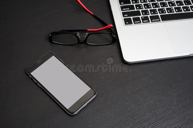 与膝上型计算机键盘和镜片的手机白色背景 免版税库存图片