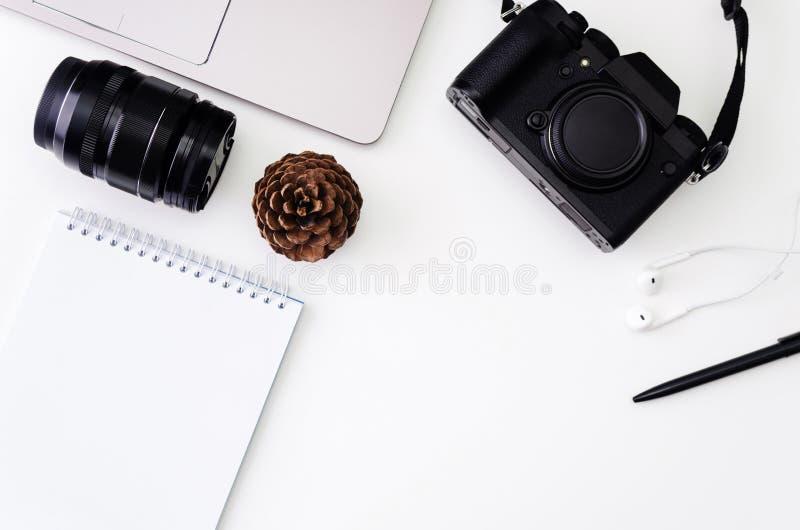 与膝上型计算机键盘,行家照相机,透镜,写的笔记薄的书桌工作区与黑笔在白色背景 平面 库存图片