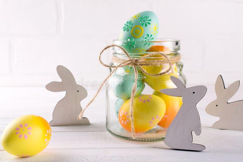 与自创复活节装饰的构成 玻璃瓶子用五颜六色的复活节彩蛋和木兔子 库存照片