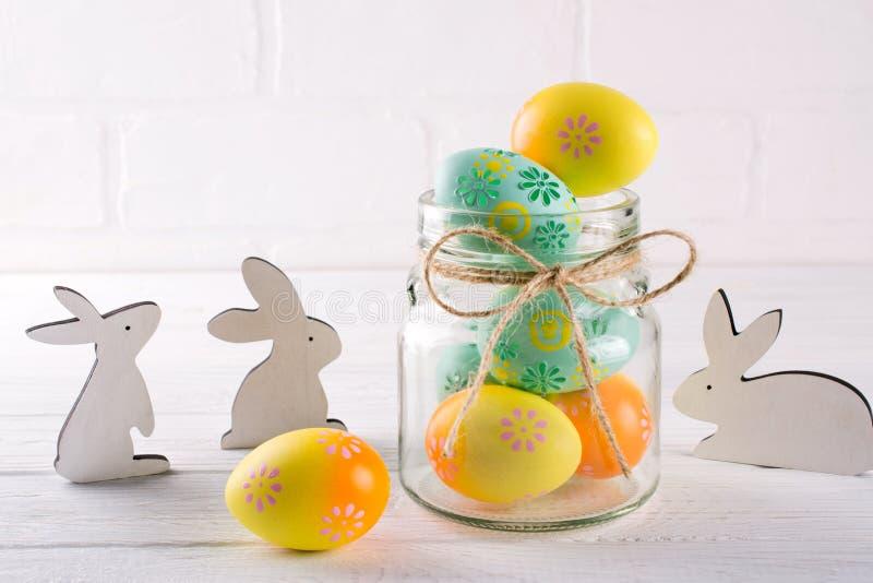 与自创复活节装饰的构成 玻璃瓶子用五颜六色的复活节彩蛋和木兔子 免版税库存照片