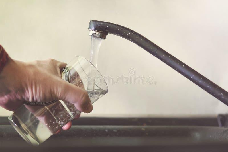 与自来水的填装的玻璃 现代龙头和水槽在家庭厨房里 倾吐新饮料的人到杯子 免版税图库摄影